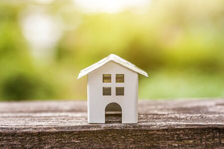 Miniature white toy model house in wooden background near green backdrop. Eco Village, abstract environmental background. Real estate mortgage property insurance dream home ecology concept Фото со стока