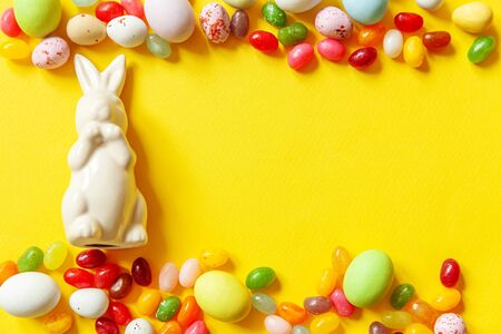 Happy Easter concept. Preparation for holiday. Easter candy chocolate eggs bunny and jellybean sweets isolated on trendy yellow background. Simple minimalism flat lay top view copy space