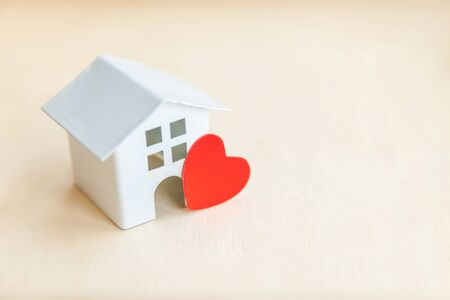 Miniature toy model house with red heart on wooden backdrop. Reklamní fotografie