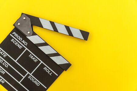 Filmmaker profession. Classic director empty film making clapperboard or movie slate isolated on yellow background. Video production film cinema industry concept. Flat lay top view copy space mock up Archivio Fotografico