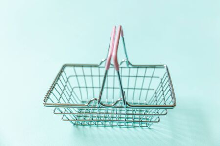 Small empty supermarket grocery shopping basket toy isolated on blue pastel colorful trendy background. Copy space. Sale buy mall market shop online shopping consumer concept 写真素材