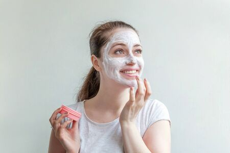 Minimal beauty portrait young woman girl portrait applying white nourishing mask or creme on face isolated on white background. Skincare cleansing eco organic cosmetic spa concept