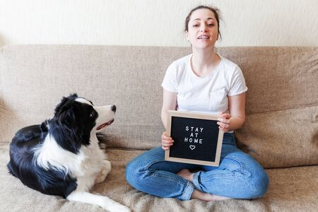 Stay Home Stay Safe. Smiling young woman playing with cute puppy dog border collie on sofa at home indoors. Girl with letter board inscription STAY AT HOME. Pet care animal life quarantine concept Stock fotó