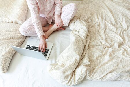 Mobile Office at home. Young woman in pajamas sitting on bed at home working using on laptop pc computer. Lifestyle girl studying indoors. Freelance business quarantine concept