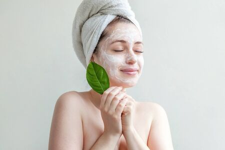 Minimal beauty portrait woman girl in towel on head applying white nourishing mask or creme on face, green leaf in hand isolated white background. Skincare cleansing eco organic cosmetic spa concept