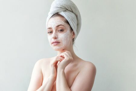 Beauty portrait of young woman in towel on head applying white nourishing mask or creme on face isolated on white background. Skincare cleansing eco organic cosmetic spa relax concept
