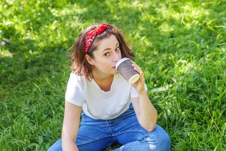 Happy girl smiling outdoor having lunch break. Beautiful young brunete woman with take away coffee cup resting on park or garden green grass background. Education freelancer resting leisure concept