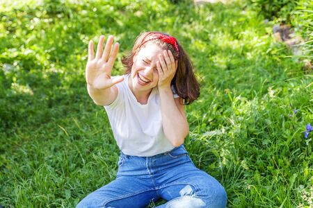 Happy girl smiling outdoor. Beautiful young brunete woman with brown hair resting on park or garden green grass background. European woman. Positive human emotion facial expression body language Stock fotó