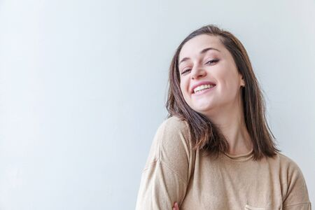 Happy girl smiling. Beauty portrait young happy positive laughing brunette woman on white background isolated. European woman. Positive human emotion facial expression body language.