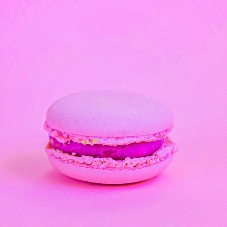 Sweet almond colorful unicorn pink macaron or macaroon dessert cake isolated on trendy pink pastel background. French sweet cookie. Minimal food bakery concept. Copy space