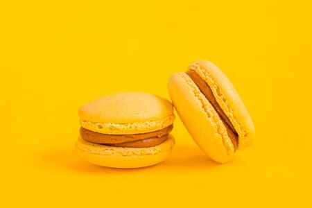 Sweet almond colorful yellow macaron or macaroon dessert cake isolated on trendy yellow modern fashion background. French sweet cookie. Minimal food bakery concept. Copy space Stock fotó