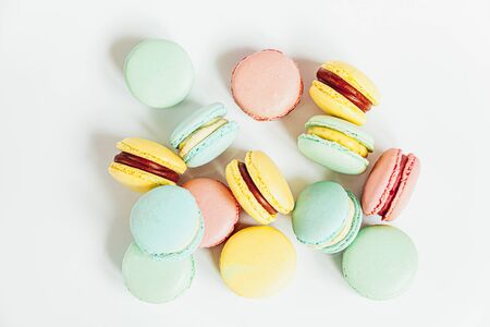 Sweet almond colorful pastel pink blue yellow green macaron or macaroon dessert cake isolated on white background. French sweet cookie. Minimal food bakery concept. Flat lay top view copy space