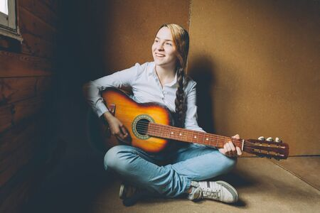 Stay Home Stay Safe. Young woman sitting in room on floor and playing guitar at home. Teen girl learning to play song and writing music. Hobby lifestyle relax Instrument leisure education concept