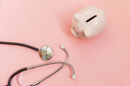 Medicine doctor equipment stethoscope and piggy bank isolated on pink pastel background. Health care financial checkup or saving for medical insurance costs concept. Flat lay top view copy space