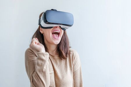 Smile young woman wearing using virtual reality VR glasses helmet headset on white background. Smartphone using with virtual reality goggles. Technology, simulation, hi-tech, videogame concept