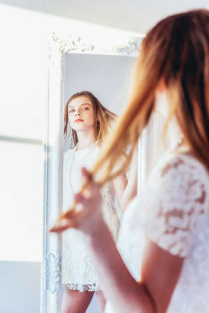 Beauty makeup morning rutine love yourself concept. Young teenage girl looking at reflection in mirror. Young positive woman wearing white dress posing in bright light room against white wall