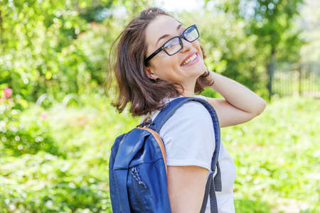 Happy beautiful positive student girl in eyeglasses with backpack smiling on green park background. Woman having rest in campus during lunch break. Education and leisure concept 免版税图像