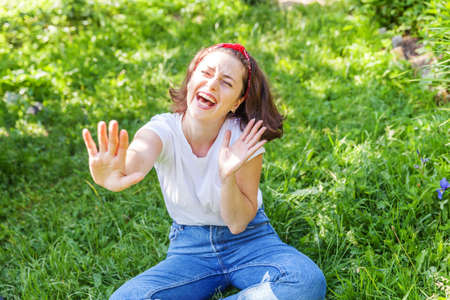 Happy girl smiling outdoor. Beautiful young brunete woman with brown hair resting on park or garden green grass background. European woman. Positive human emotion facial expression body language 免版税图像