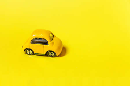 Simply design yellow vintage retro toy car isolated on yellow colorful background. Automobile and transportation symbol. City traffic delivery concept. Copy space