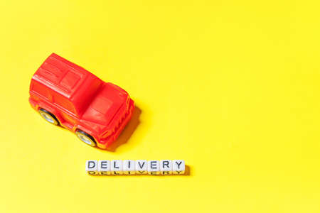 Simply design red toy car and inscription DELIVERY word isolated on yellow colorful background. Internet shopping online purchase e-commerce packages delivery service concept. Copy space