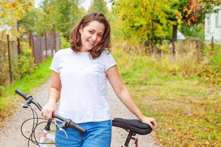 Young woman riding bicycle in summer city park outdoors. Active people. Hipster girl relax and rider bike. Cycling to work at summer day. Bicycle and ecology lifestyle concept Zdjęcie Seryjne
