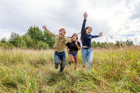 Summer holidays vacation happy people concept. Group of three friends boy and two girls running and having fun together outdoors. Picnic with friends on road trip in nature