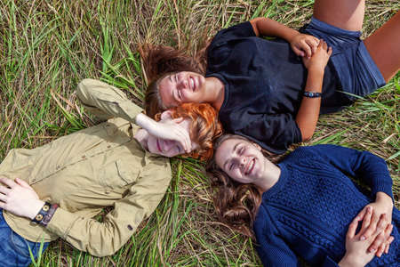 Summer holidays vacation happy people concept. Top view group of three friends lying on grass in circle smiling and having fun together outdoors. Picnic with friends on road trip in nature