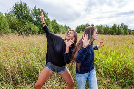 Summer holidays vacation happy people concept. Group of two girl friends sisters dancing hugging and having fun together in nature outdoors. Lovely moments best friend Zdjęcie Seryjne