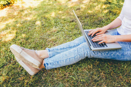 Freelance business concept. Woman legs on green grass lawn in city park, hands working on laptop pc computer. Lifestyle authentic candid student girl studying outdoors. Mobile Office Zdjęcie Seryjne