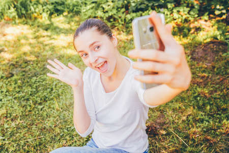 Young funny girl take selfie from hands with phone sitting on green grass park or garden background. Portrait of young attractive woman making selfie photo on smartphone in summer day