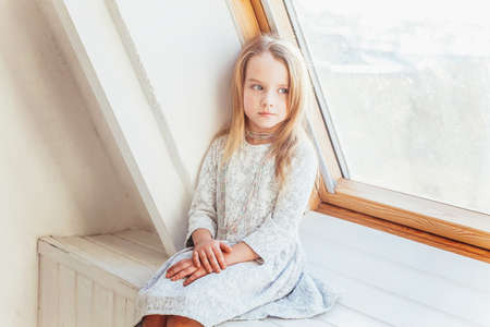 Little cute sweet smiling girl in white dress sitting on window sill in bright light living room at home indoors. Childhood schoolchildren youth relax concept