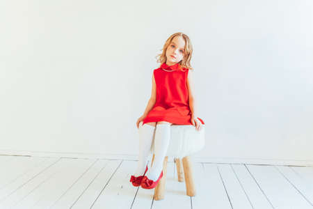 Sweet little girl in red dress sitting on chair against white wall at home, relaxing in white bright living room indoors. Childhood schoolchildren youth relax concept