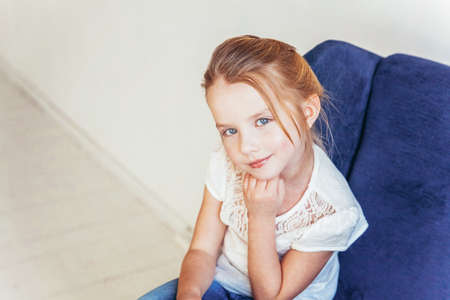 Sweet little girl in jeans and white T-shirt sitting on modern cozy blue chair relaxing in white bright living room at home indoors. Childhood schoolchildren youth relax concept