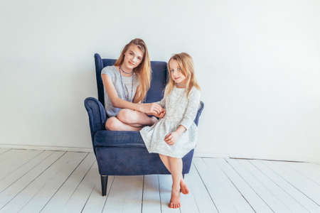 Two happy kids sitting on cozy blue chair relaxing playing in white living room indoors. Little girl playing with teenage girl showing her love care. Sisters having fun at home