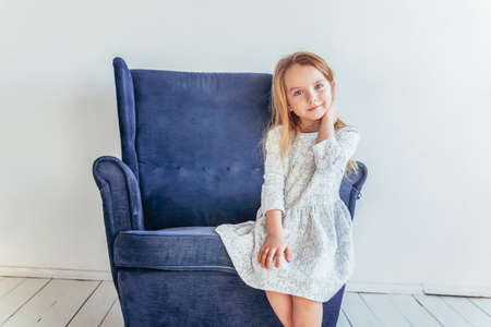 Sweet little girl in white dress sitting on modern cozy blue chair relaxing in white bright living room at home indoors. Childhood schoolchildren youth relax concept