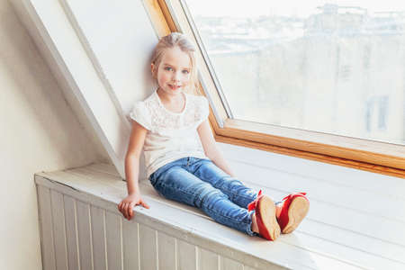 Stay Home Stay Safe. Little cute sweet smiling girl in jeans and white T-shirt sitting on window sill in bright light living room at home indoors. Childhood schoolchildren youth relax concept Zdjęcie Seryjne