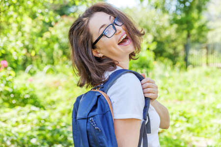 Happy beautiful positive student girl in eyeglasses with backpack smiling on green park background. Woman having rest in campus during lunch break. Education and leisure concept Zdjęcie Seryjne