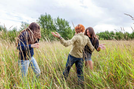 Summer holidays vacation happy people concept. Group of three friends boy and two girls dancing and having fun together outdoors. Picnic with friends on road trip in nature
