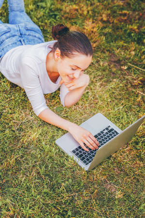 Mobile Office. Freelance business concept. Young woman lying on green grass lawn in city park working on laptop pc computer. Lifestyle authentic candid student girl studying outdoors. 免版税图像