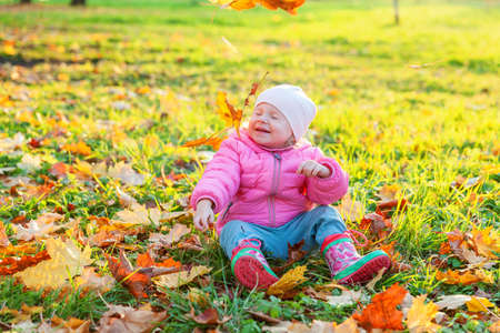Happy young girl playing under falling yellow leaves in beautiful autumn park on nature walks outdoors. Little child throws up autumn orange maple leaves. Hello autumn concept Фото со стока