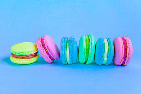 Sweet almond colorful pink blue yellow green macaron or macaroon dessert cake isolated on trendy blue pastel background. French sweet cookie. Minimal food bakery concept. Flat lay top view copy space