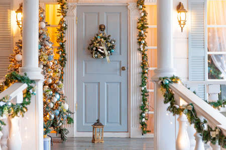 Christmas porch decoration idea. House entrance decorated for holidays. Golden and green wreath garland of fir tree branches and lights on railing. Christmas eve at home. Reklamní fotografie