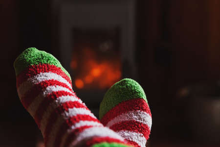 Feet legs in winter clothes wool socks at fireplace background. Woman sitting at home on winter or autumn evening relaxing and warming up. Winter and cold weather concept. Hygge Christmas eve