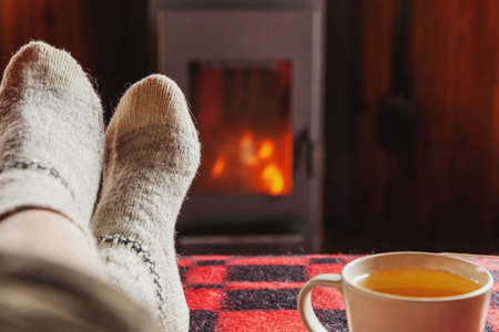 Feet legs in winter clothes wool socks and cup tea at fireplace background. Woman sitting at home on winter or autumn evening relaxing and warming up. Winter and cold weather concept. Hygge Christmas eve