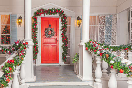 Christmas porch decoration idea. House entrance with red door decorated for holidays. Red and green wreath garland of fir tree branches and lights on railing. Christmas eve at home.