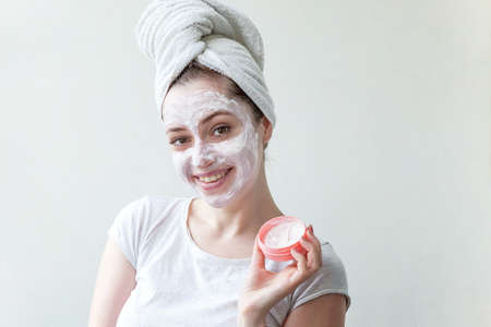 Beauty portrait of woman in towel on head with white nourishing mask or creme on face, white background isolated. Skincare cleansing eco organic cosmetic spa relax concept