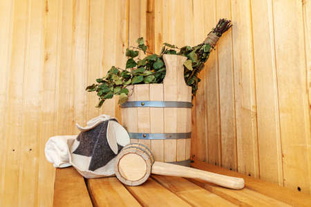 Interior details Finnish sauna steam room with traditional sauna accessories basin birch broom scoop felt hat towel. Traditional old Russian bathhouse SPA Concept. Relax country village bath concept