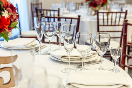 Fancy table set for dinner with napkin glasses in restaurant, luxury interior background. Wedding elegant banquet decoration and items for food arranged by catering service on white tablecloth table