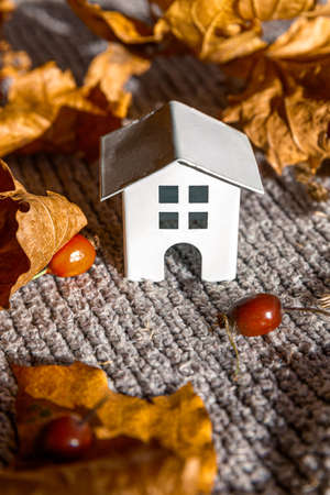 Autumnal Background. Toy house and dried orange fall maple leaves on grey knitted sweater. Thanksgiving banner copy space. Hygge mood cold weather concept. Hello Autumn with family. Banque d'images