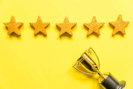 Simply flat lay design winner or champion gold trophy cup and 5 stars rating isolated on yellow background. Victory first place of competition. Winning or success concept. Top view copy space